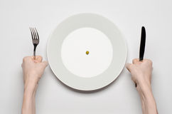 Healthy food theme: hands holding knife and fork on a plate with green peas on a white table top view Royalty Free Stock Image