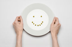 Healthy food theme: hands holding a plate of green peas on a white table top view. Studio royalty free stock image