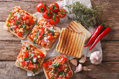 Healthy food: toast with white beans, tomatoes, cheese and garlic close-up. horizontal top view. Healthy food: toast with white beans, tomatoes, cheese and royalty free stock photo
