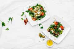 Healthy food. Two white plates. Tomato salad, arugula, spinach, olives, pepper. White background royalty free stock image