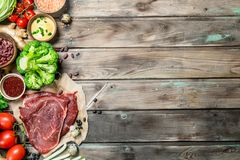 Healthy food. Variety of organic food with raw beef meat. On a wooden background royalty free stock images