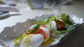 Healthy food and vegetarian concept. Close up of pouring olive oil over caprese salad. Italian caprese salad with. Mozzarella cheese. Ultra Slow motion stock video
