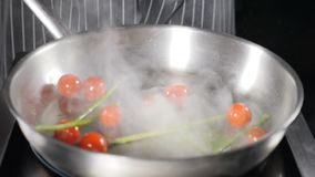 Healthy food and vegetarian concept. Tomato cherry and asparagus are falling in slow motion into hot frying pan. Dense stock video