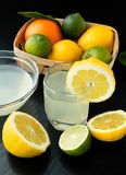 Healthy food and vitamins: fresh lemon and lime orange with leaves and freshly squeezed delicious juice in a glass bowl on. A black table royalty free stock images