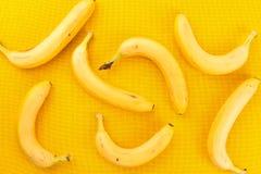 Healthy food and vitamins: many yellow ripe bananas lie on yello Stock Photography