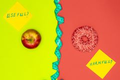 Healthy food vs harmful snacks. Choice concept. Apple, Donut and measure tape. Living coral flat lay.  royalty free stock images