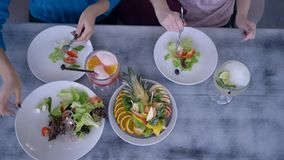 Healthy food for weight loss at fresh party, top view on young women having dinner and serving salad at table with