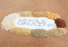 Healthy Food Whole Grains on Wooden Background. Whole grains, which are healthy food, indicated by text handwritten using pencil, including sorghum, wheat, corn Royalty Free Stock Image