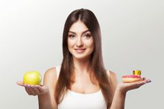 Healthy food. The woman is losing weight. A young girl hesitates. Between choosing food or sports. The Concept of Health and Beauty. On a gray background Royalty Free Stock Photos