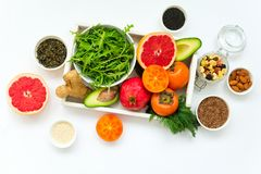 Healthy food in wooden tray: fruits, vegetables, seeds and greens on white background. Flat lay. Top view Stock Image