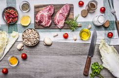 Healthy foods, cooking concept pork steak with vegetables,knife, fruits, spices, laid out frame place for text, on wooden rusti Stock Images