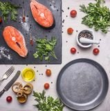 Healthy foods, cooking and sport concept Two fresh salmon steak with herbs and spices on  cutting board stone, laid near cherry t. Healthy foods, cooking and Royalty Free Stock Photography