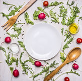 Healthy foods, cooking and vegetarian concept arugula salad, wooden spoon and fork for  salad, radishes, cherry tomatoes, seaso Royalty Free Stock Photo