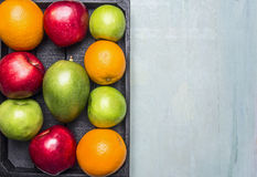 Healthy foods fresh ripe fruit, apples of different varieties, oranges, mangoes wooden box border ,text area  on wooden ru Royalty Free Stock Photography