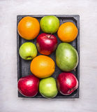 Healthy foods fresh ripe fruit, apples of different varieties, oranges, mangoes in wooden box border , wooden rustic background Royalty Free Stock Photos
