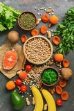 Healthy foods high in potassium. A variety of legumes, salmon, fruits, vegetables, dried apricots, seaweed chuka and nuts on a