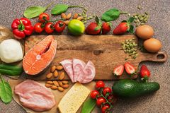 Healthy foods low in carbohydrates. Keto diet concept. Salmon, chicken, vegetables, strawberries, nuts, eggs and tomatoes, cutting. Board. Top view stock photography