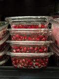 Healthy foods at the market: Red pomegranate seeds for sale. Four packages stacked in profile.