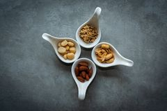 Healthy Foods. Mixed nuts in white bowls with nuts for diet on a concrete table. Different kinds of tasty and healthy nuts. royalty free stock images