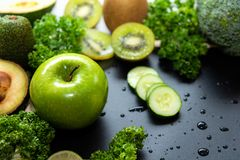 Healthy Foods. Organic and Fresh green vegetable for detox, diet and weight loss on the black background. royalty free stock photos