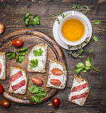 Healthy foods sandwiches with red fish, cherry tomatoes and salami on a cutting board, cup of tea with thyme on wooden rust. Healthy foods sandwiches with red royalty free stock image