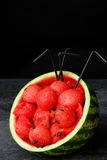 Healthy, fresh and beautiful watermelon. Red watermelon scoops with straws on a black background. Tasty summer juices. Copy space. Royalty Free Stock Image