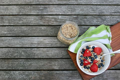 Healthy Fresh Breakfast Bowl with Berries. Granola in white bowl with greek yogurt and berries on wooden background, top view, type space, horizontal Stock Photo