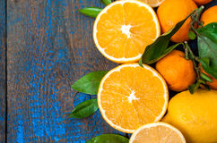 Healthy fresh citrus juice two glasses, oranges, tangerines, lemons, ice, leaves. Stock Photos