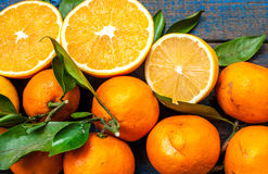 Healthy fresh citrus juice two glasses, oranges, tangerines, lemons, ice, leaves. Stock Photos