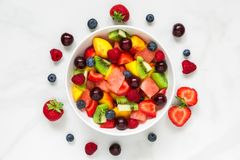 Healthy fresh fruit and berry salad in a bowl on white marble background. healthy food Stock Image