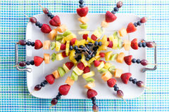 Healthy fresh fruit kebabs on a picnic table Royalty Free Stock Photo