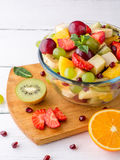 Healthy fresh fruit salad in glass bowl on white wooden background. Stock Images