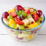 Healthy fresh fruit salad in glass bowl on white wooden background. Stock Photography