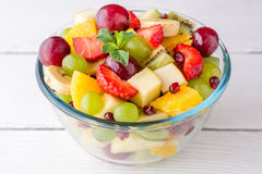 Healthy fresh fruit salad in glass bowl on white wooden background. Royalty Free Stock Photography