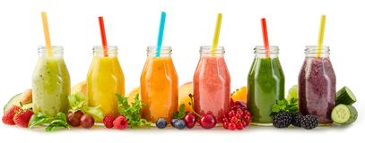Healthy fresh fruit smoothies with ingredients. Row of healthy fresh fruit and vegetable smoothies with assorted ingredients served in glass bottles with straws royalty free stock images