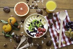 Healthy fresh natural breakfast with yoghurt, fruits, juice and nuts on wood table. Top view. Concept about fresh ingredients and stock image