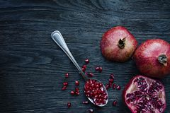Healthy fresh pomegranates on a dark wooden background. A spoon with grains of fresh pomegranate. Vibrant focus. Dark wooden royalty free stock photo