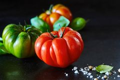 Healthy fresh ripe red tomato with seasoning. Healthy whole wet fresh ripe red tomato with water droplets and seasoning on a black reflective background with Stock Photos