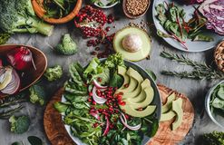 Healthy fresh salad with avocado, greens, arugula, spinach, pomegranate in plate over grey background. Healthy vegan food,. Clean eating, dieting, top view royalty free stock photos