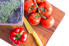 Healthy fresh salad ingredients on a cutting board. Healthy fresh salad ingredients on a chopping board with a sharp paring knife with three varieties of lettuve Royalty Free Stock Photos