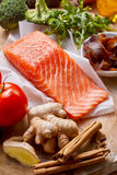 Healthy fresh salmon rich in omega-3 fatty acids. Raw fresh salmon rich in omega-3 fatty acids with stick cinnamon, root ginger , tomato, rocket and broccoli in stock image