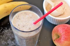Healthy fresh smoothie drink from red apple, banana chia seeds and plant protein powder in the glass with straw Stock Photography