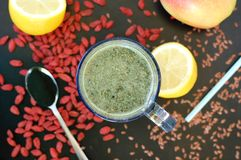 Healthy fresh smoothie drink from red Chinese berry goji, lemon, green spirulina, linseed and apple Stock Photos