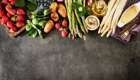 Healthy fresh spring fruit and vegetable border. On textured slate with strawberries, blueberries, potatoes, basil and green and white asparagus shoots with stock photos