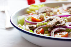Healthy fresh summer salad with letucce, radish, cherry tomatoes, red onion and champignons with italian herbs on a table Stock Images