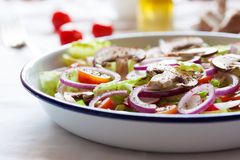 Healthy fresh summer salad with letucce, radish, cherry tomatoes, red onion and champignons with italian herbs on a table Stock Photo