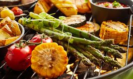 Healthy fresh summer vegetables grilling on a BBQ. Outdoors in the garden with zucchini, potato wedges, asparagus, tomato and corn on the cob garnished with stock photo