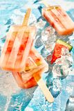 Healthy fresh fruit red melon frozen popsicles. Healthy fresh t red melon frozen popsicles stacked on a bed of crushed ice for a refreshing summer treat for kids Royalty Free Stock Images
