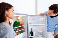 Healthy fridge couple. Healthy eating couple get fresh vegetables out of the fridge to cook food Stock Images