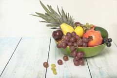 Arranged fruit bowl on the table. Healthy fruit background ; Studio photo of different fruits on white and  blue  vintage wooden table , high resolution product Royalty Free Stock Photography